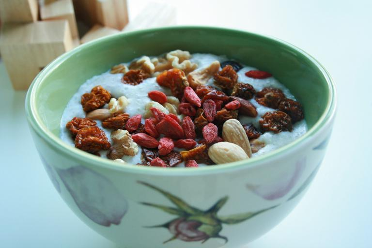 zdravá snídaně – miska s kaší a posypaná zdravými surovinami – včetně mandlí